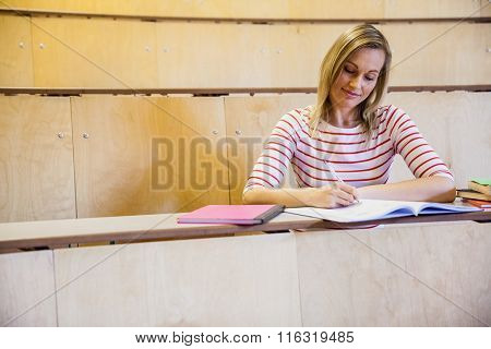 Focused female student writing notes at the university