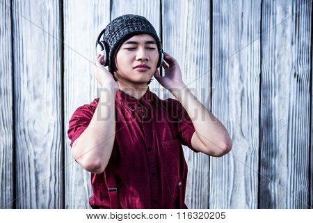 Hipster listening music with headphone on wooden bakground