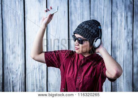 Hipster listening music with headphone while holding a smartphone on wooden bakground