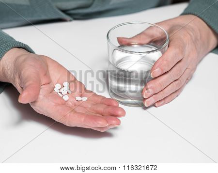 Senior Woman With  Pills And Glass Of Water At Home