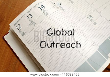 Global outreach text concept write on notebook with pen
