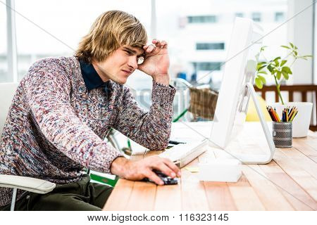 Troubled hipster businessman sitting in his office and holding his head