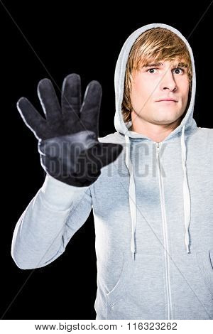 Man with black gloves staring at camera with black background