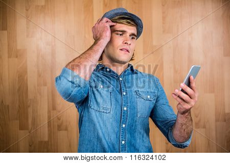 Concerned hipster looking at smartphone against wooden wall