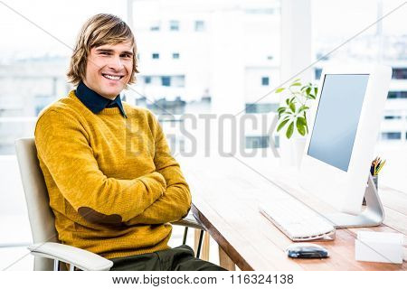 Smiling hipster businessman crossing arms in his office