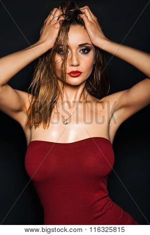 Hot young woman model with sexy bright red lips makeup, strong eyebrows, clean shiny skin and wet ha