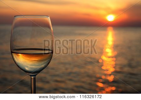 Glass of white wine in the sunset overlooking the sea