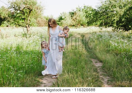 Mom hugging two daughters outdoors