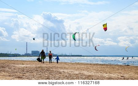 Family Walking On Beach. Kitesurfers Ride The Waves