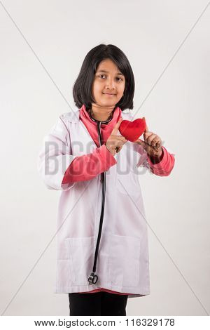 indian girl doctor with toy heart, asian girl child doctor with stethoscope and heart toy, heart sof