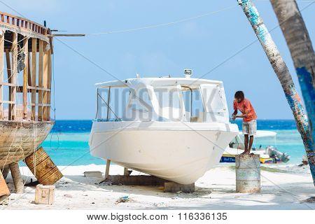 MAAFUSHI, MALDIVES - JANUARY 5: Craftsman repairs a speedboat to be ready for a new tourist season