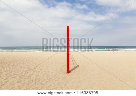 red volleyball post at the beach under sky