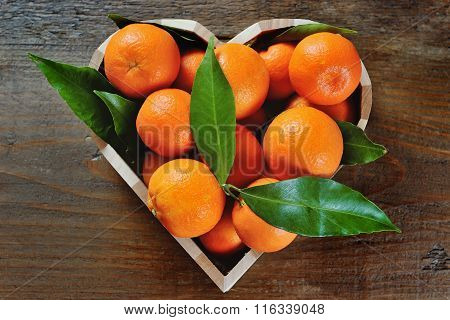 Juicy Clementines In A Heart Shaped Box On A Wooden Background