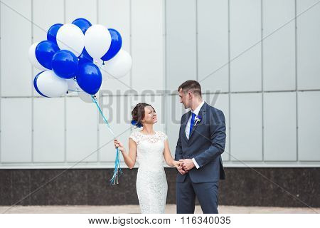 Happy bride and groom celebrating wedding day with balloons