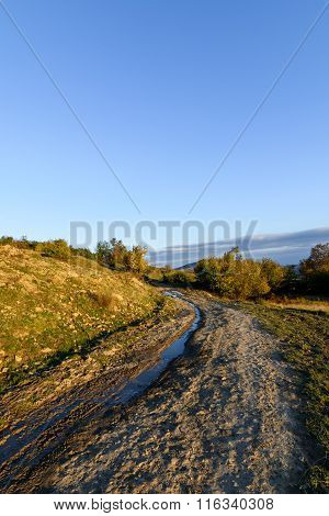 Vertical View Over Rural Road In Autumn Landscape. Mountain Rural Road With Water And Mud, Blue Sky