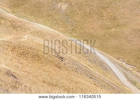 Rural Road In Autumn Mountain Landscape. Background Mountain Rural Road Over Hills With Dry Grass..