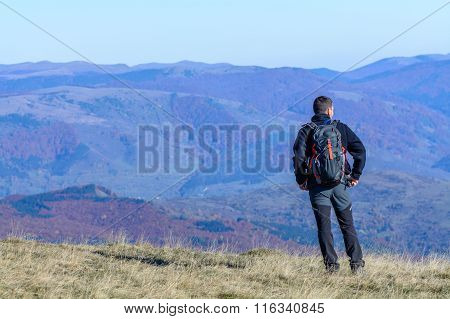 Young Tourist Man Standing On Mountain.  Happy Young Tourist Man With Backpack Standing On Rocky Cli