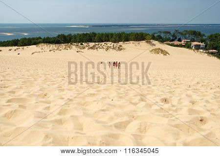 PYLA-SUR-MER, FRANCE - JUNE 27, 2013: People walk at the dune of Pilat in a summer day against Atlantic ocean. This dune is the biggest one in Europe, and it still grow