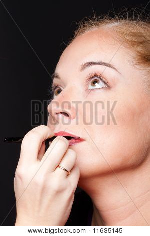 a visagiste inflicts a make-up to the  woman
