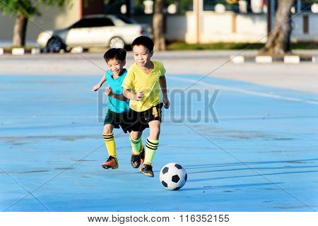 Boy Play Football On The Blue Concrete Floor.