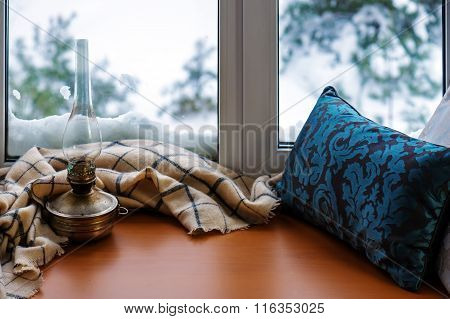 Beige Woolen Scarf And Old Lamp Located On Stylized Wooden Window Sill.