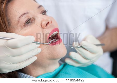 Skillful male dental doctor is working with patient