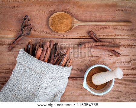 Composition Of Cinnamon Stick In Hemp Sack And Cinnamon Powder In White Mortar And  Cinnamon Powder