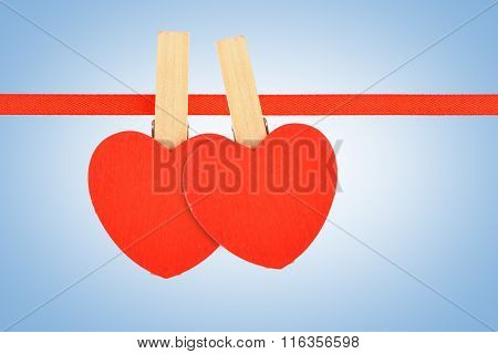 Two Red Hearts At Ribbon Over Blue Noise