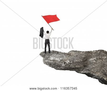 Businessman Cheering And Waving Red Flag On Top Of Cliff