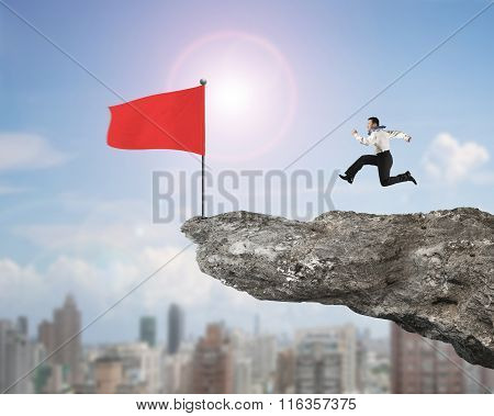 Man Running For Red Flag On Cliff With City View