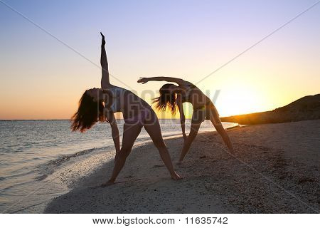 Girls Practicing Yoga  Against Sunrise
