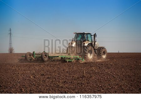 View Of Tractor Seeder Sowing In Ploughed Field