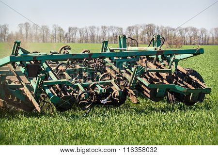 Closeup Weeding-machine Behind Tractor On Green Wheat Field