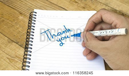 Thank you wording on a book by hand on wooden background