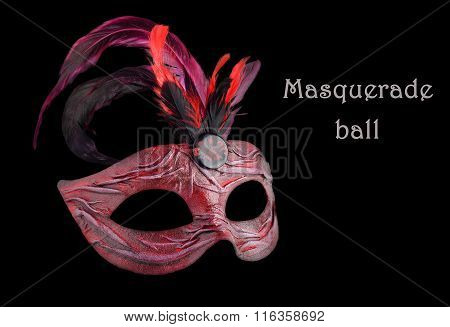 Venetian red Carnival half mask with feathers, at black background.