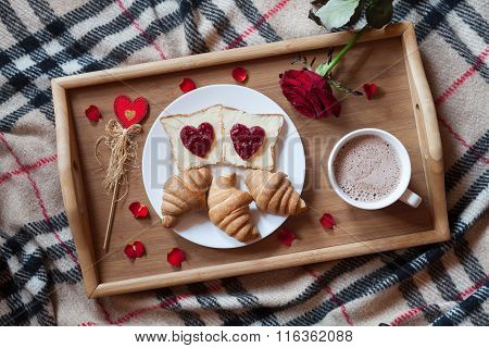 Romantic breakfast in bed for Valentines Day. Toasts with jam, croissants, hot chocolate, red rose f