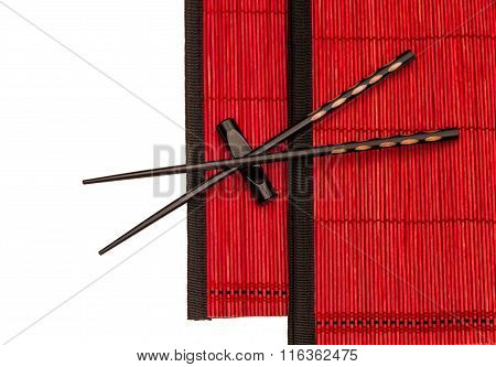 Chinese chopsticks on red bamboo mat. Asian style table place setting