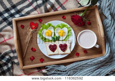 Romantic valentines day breakfast in bed with heart-shaped eggs, toasts, jam, coffee, rose and petal