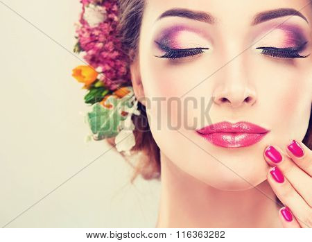 Girl with delicate flowers in hair and fashion fuchsia manicurenail