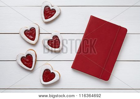 Heart shaped cookies with empty red notebook, composition on white wooden background for Valentines