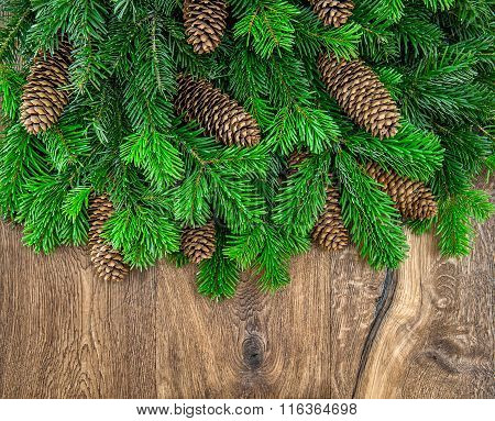 Christmas Tree Branches With Cones Over Wooden Background