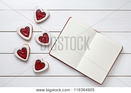 Shortbred heart shaped cookies with empty notebook frame, composition on white wooden background for