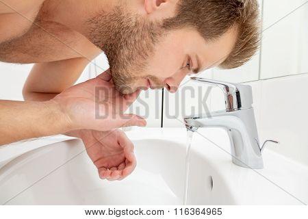 Man Washing Face In Bathroom Sink