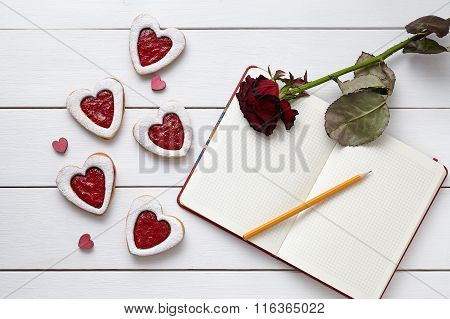 Heart shaped cookies with empty notebook, pencil and red rose gift on white wooden background.