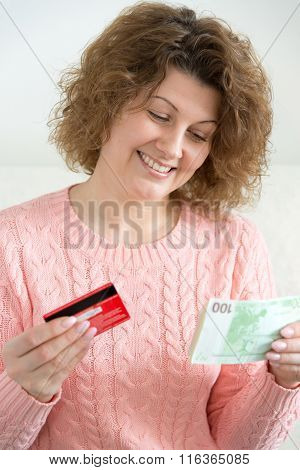 adult woman holding money and credit cards