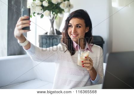 Woman making self portrait with a cell phone camera in restaurant taking picture on smart phone.