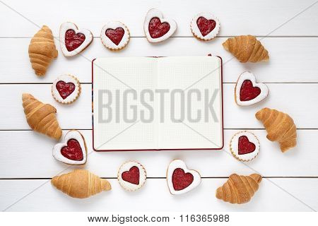 Empty notebook frame for design text, croissants and heart shaped cookies composition on Valentines