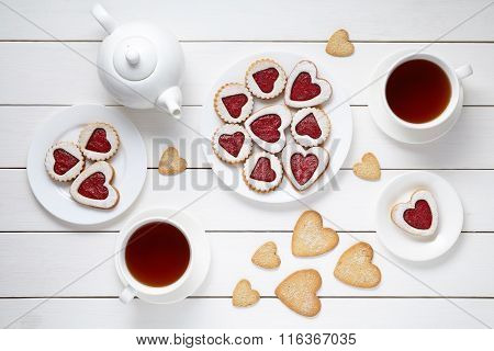 Sweet heart cookies for Valentines day with teapot and two cups of tea composition on white wooden b