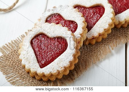 Round shortbread cookies with heart shaped jam close-up composition for Valentines Day