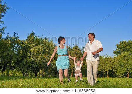 Family And Relationships Concepts. Happy Young Family Of Three Running Together Outdoors On Nature.